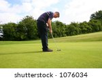 A junior golf champion putts in for a birdie - stock photo