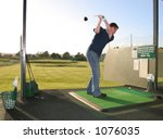 A junior golf champion practices on the golf range - stock photo