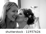 mother and daughter kissing before the wedding. - stock photo