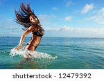 Young woman in bikini splashing in ocean - stock photo