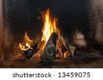 Firewood blaze in heater. Brick wall - stock photo