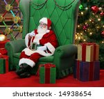 authentic santa claus sitting in large green chair surrounded by presents and decorations - stock photo