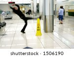 Man slips next to Wet Floor sign - stock photo