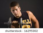 Muscular young man lifting weights - stock photo