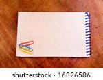 Spiral Notepad, and clips over wood table - stock photo