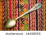 Spoon of silver on tapestry - stock photo