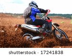 Off-road motorbike extreme cornering. Motion blur with flying dirt. - stock photo