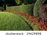 beautiful lawn and hedge, trimmed with flowers - stock photo