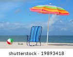 Beach chair, ball and umbrella on a summer day. - stock photo