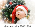 Little girl in red Santa hat wishing under christmas tree with snowflakes - stock photo