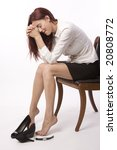 Woman in skirt and blouse sitting on chair crying after bad day - stock photo