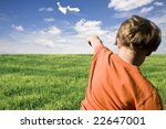 young boy flying a paper airplane - stock photo