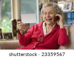 Happy senior woman holding photo and cell phone - stock photo