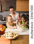 Mother teaching two little girls how to cook - stock photo