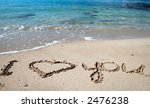 Love message on gold sand and sea waves - stock photo