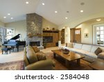 living room in custom home,stone fireplace,grand piano,big screen,archways,contemporary furnishings - stock photo