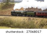vintage steam train passing through countryside with identification markings removed - stock photo