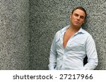 Attractive male next to a gray wall - stock photo