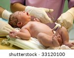 New born baby being treated just after the birth - stock photo