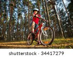 Little girl riding on bicycle in the forest, low angle view. - stock photo
