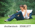 Two young girls sitting on the grass and reading books - stock photo