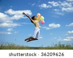 Happy young woman flying with colorful balloons - stock photo