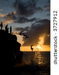 Multiple people jumping off a rock in Waimea Beach - stock photo