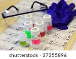 Different chemicals, safety glasses, and gloves on a periodic table. - stock photo
