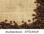 Textured background of coffee beans and sandy brown burlap cloth - stock photo