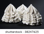 Three caramel meringues on black canvas - stock photo