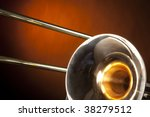 A gold brass trombone wind music instrument isolated against a yellow gold spotlight in the horizontal format. - stock photo