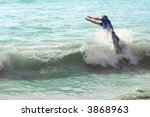 A young man diving into the waves - stock photo