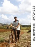 VINALES, CUBA - MARCH 20: Man walks with old rusty bike in Cuban countryside in Vinales on March 20, 2009. Most Cubans live way below established poverty lines, the issue is biggest in rural areas. - stock photo