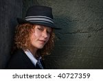 Beautiful blonde woman in hat posing against concrete wall - stock photo