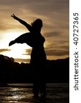 Silhouette of woman dancing with sunset in background - stock photo