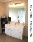 A white and stainless steel modern bathroom vanity, mirror and accessories. - stock photo