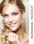Beautiful Blond bride with blue eyes wearing diamond jewelery - stock photo