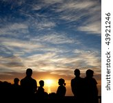 Men, women, and children watching the sunset - stock photo