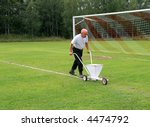 Caretaker painting chalk lines on soccer field - stock photo