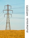 Electricity pylon in wheat field - stock photo