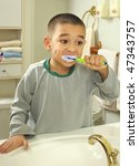 Six-year-old boy brushing teeth in the bathroom - stock photo