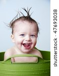 Baby bathing in green tub - stock photo