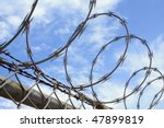 Barbed wire fence with blue sky and white clouds. - stock photo