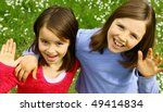 Two sisters waving - stock photo