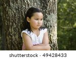 Cute little Asian girl in a white and pink dress, pouting by tree - stock photo
