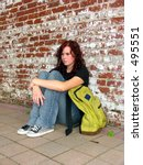 Girl with bookbag sitting against a brick wall - stock photo