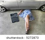 Young woman fixing a car in a garage. - stock photo