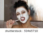 Portrait of a beautiful young woman in the bathroom with a beauty facial mask and brushing her teeth. - stock photo
