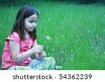 One girl about to blow on dandelion - stock photo