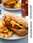 cheese steak sandwich accompanied by fries and an ice cold cola - stock photo